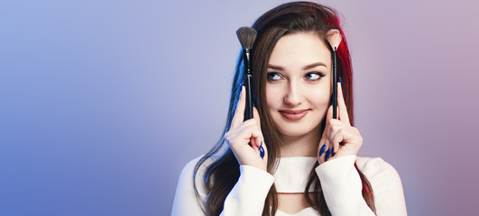 Wall Mural - studio portrait of a cute girl with makeup brushes on head like horns, face of funny young woman, concept of female beauty and cosmetics