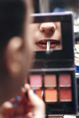 Wall Mural - reflection of a female lips with lipstick in a palette mirror with, girl doing makeup indoors, drawing a contour, concept of beauty and cosmetics