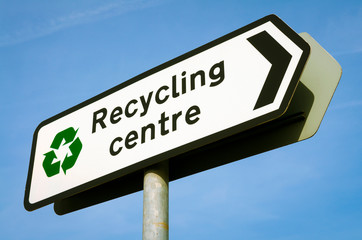 Sign pointing the way to the Recycling Centre standing in bright blue sky