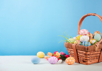 Happy easter, Easter painted eggs in the basket on wooden rustic table for your decoration in holiday. copy space.
