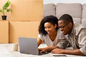 Smile african american man and woman looking at laptop - fototapety na wymiar