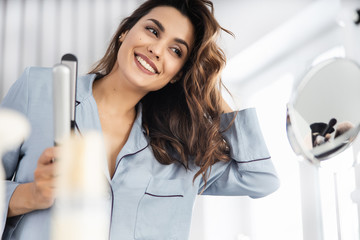 Happy pretty woman holding curling iron at home