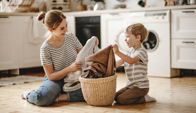 happy family mother housewife and child   in laundry with washing machine .