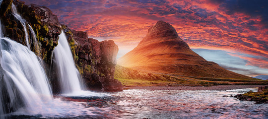 Wall Murals Pale violet Mount Kirkjufell with dramatic sky in Iceland.Summer sunset over the famous Kirkjufellsfoss Waterfall with Kirkjufell mountain in the background in Iceland. Long exposure. Picturesque epic scenery