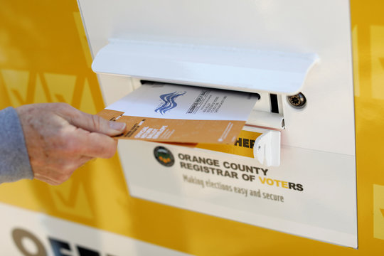 A voter drops ballots for the March 3 Super Tuesday primary into a mobile voting mail box in Laguna Woods, California