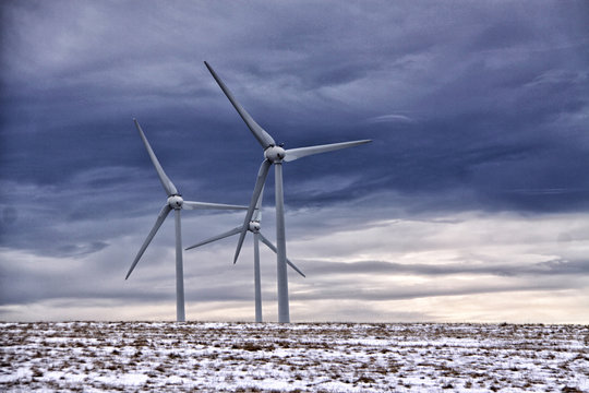 Three wind power stations agains cloudy sky