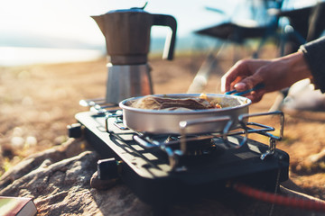 Fototapeten Camping moka pot coffee campsite morning lifestyle, person cooking hot drink in nature camping outdoor, cooker prepare breakfast picnic, tourism recreation outside