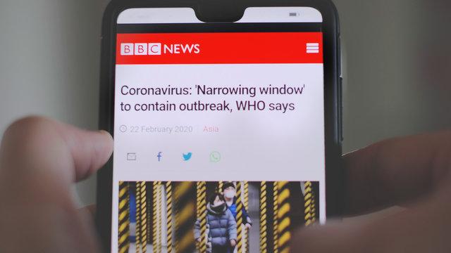 Hands on smartphone read the Coronavirus covid-19 news BBC article