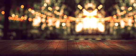 top desk with blur party or restaurant  background,long wooden table and blurred bokeh of night street background