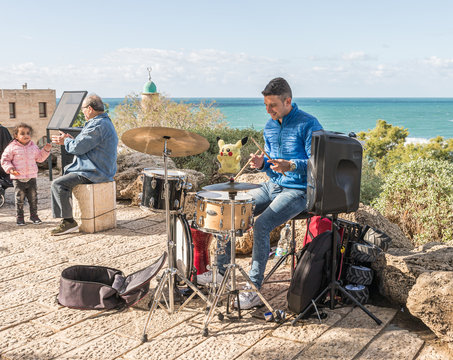 Street musician plays on a drum set on the promenade in old Yafo in Israel