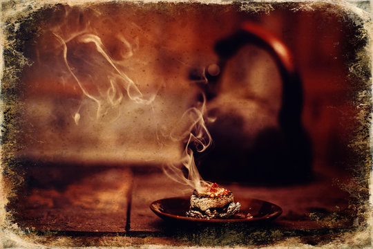 Frankincense burning on a hot coal. Aromatic frankincense. Old photo effect.
