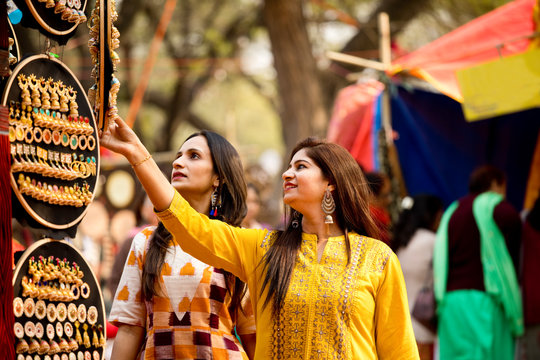 Two women shopping for earrings at street market
