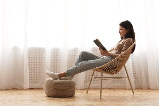 Relaxed girl reading book sitting in chair by the window