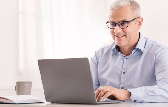 Senior man using laptop at office and typing
