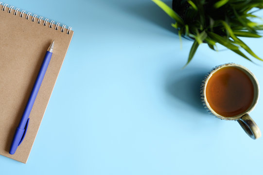 notebook or sketchbook made of craft paper and a pen and tea cup and green plant on a blue background. space for text