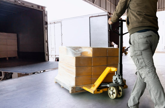 Worker courier unloading cargo pallet shipment goods, package box, his using hand pallet  jack load into a truck, Road freight transport, Warehouse industrial delivery shipment and logistics