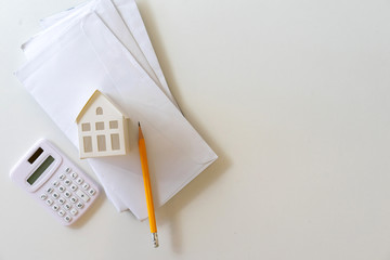 close up top view on house's model on mail letter with calculator and pencil on table for expense of home loan mortgage and home utilility , economy and financial concept