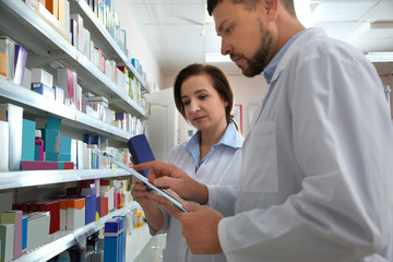 Papiers peints Pharmacie Professional pharmacists near shelves with medicines in modern drugstore
