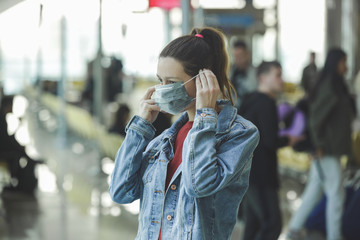 Woman wearing protective mask in airport, Coronavirus contagion fears concept