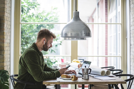 Male entrepreneur using laptop while holding phone at home office
