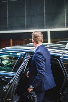 Mature entrepreneur entering in car