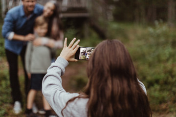 Girl taking picture of family with mobile phone while standing in backyard