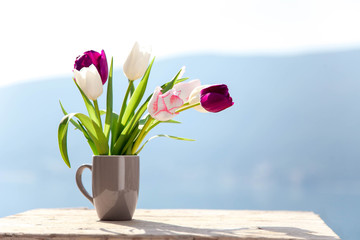 Fotomurales - Spring flowers on balcony at blue background of mountains. Tulips on wooden table outdoors. Still life at sea beach. Blooming Pink, white, purple bouquet. Copy space.