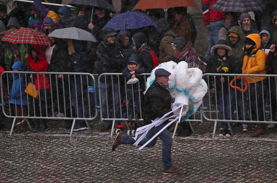 """A man runs under heavy rain while carrying an ostrich feather adorned hat worn by the """"Gilles of Binche"""" performers during the Binche carnival,"""