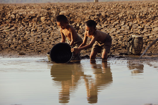An Asian boy in a dry area is using a plastic bucket to draw water from the final water source. Concept of shortage of clean water from global warming