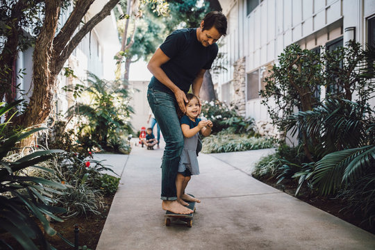 Father and daughter skateboarding on footpath