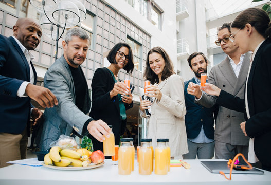 Smiling male and female business executives with juice outside office