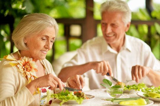 Portrait of happy senior couple having diner and posing on the veranda