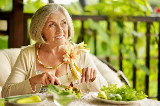 Beautiful senior woman eating healthy breakfast