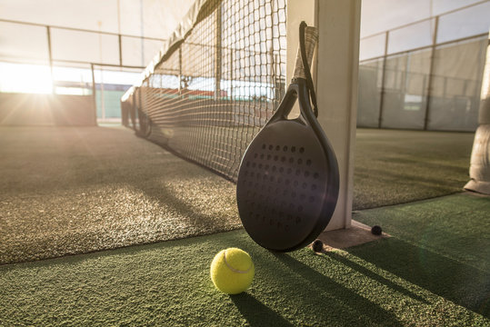 Paddle tennis racket and ball in sunset image