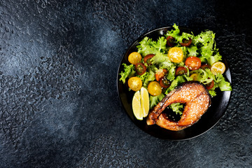 Foto op Canvas Gebakken Eieren Grilled red fish steak, salmon, salmon with fresh salad of greens and cherry tomatoes on a black background.