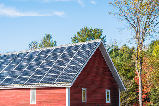 Solar panels on the roof of a red wooden barn on a sunny autumn day. Concept of alternative energy. Countryside of Vermont, USA.