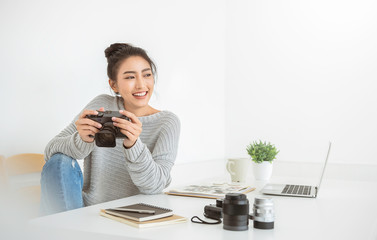 Portrait of beautiful asian photographer woman workingoffice desk holding camera with laptop. Business people employee freelance online marketing.  Successful freelance creative artist girl concept Fotomurales