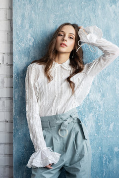 Fashionable woman wearing trendy vintage style white blouse, light blue high waist trousers. Spring, summer fashion concept