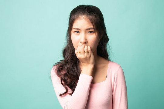 Unsure hesitant nervous young asian  woman biting her fingernails.