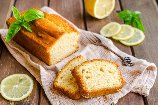 Lemon pound cake on rustic wooden background with lemon.