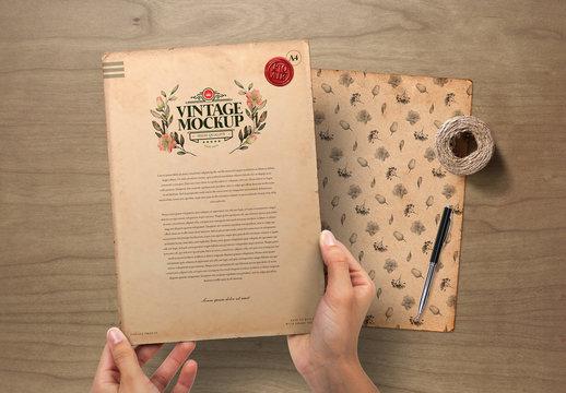 Hands Holding Vintage Paper on Wooden Background Mockup