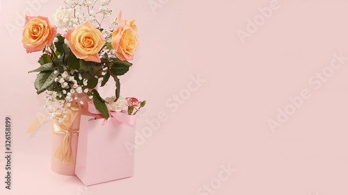 Roses with a gift on a pink table, abstract spring floral background. Creative modern bouquet, minimal holiday concept. Greeting card for Women's Day or Mother's Day, happy birthday, wedding,