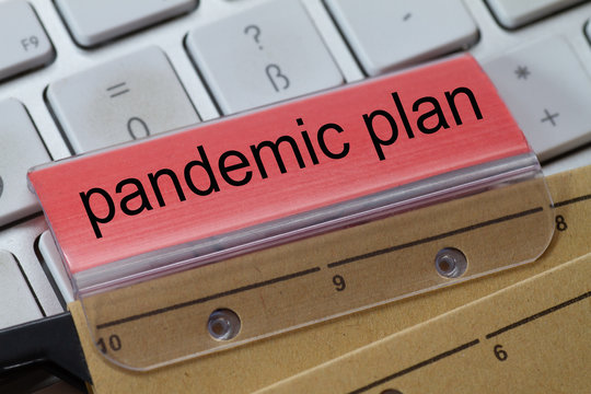 The words  pandemic plan can be seen on the label of a brown hanging folder. The hanging folder is on a computer keyboard.