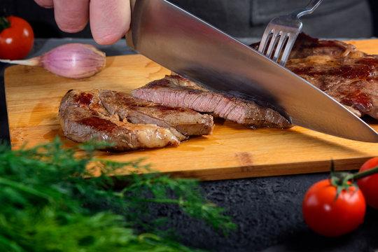 Freshly prepared beef steak is cut into slices. The meat is medium rare.