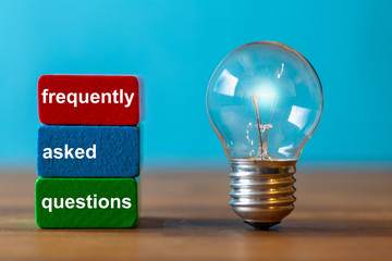 frequently asked questions are the word written on a red and a green toy block. Next to the tow blocks, an ancient light bulb with glowing light stands freely and upright on a dark wooden table.
