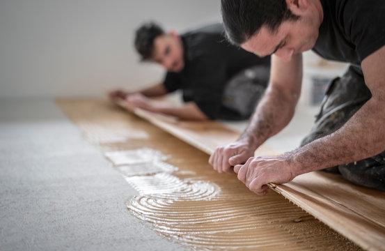 zwei Handwerker verlegen Parkettboden