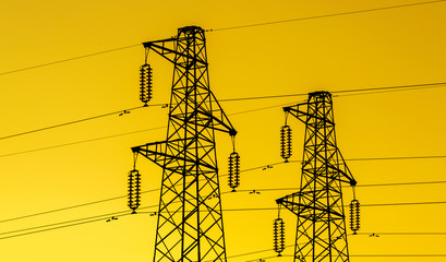 lectric power industry. Transmission towers or electricity pylons with golden sky background