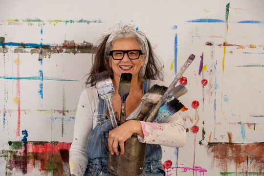 smiling older woman, proud artist, in her fifties with grey hair and glasses and many paintbrushes