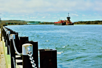 A tugboat pushes a barge in the Cape Cod canal with the Sagamore bridge in the background