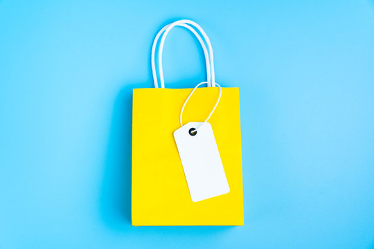Single yellow gift or shopping bag with blank label tag isolated on blue background